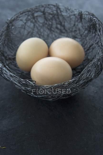 Сырые яйца в провод Пасха гнездо — стоковое фото