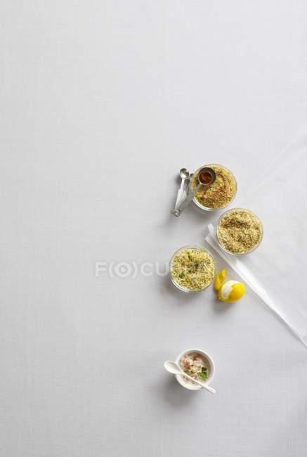 Vista superior de cuencos pequeños de diferentes especias e ingredientes sobre superficie blanca - foto de stock