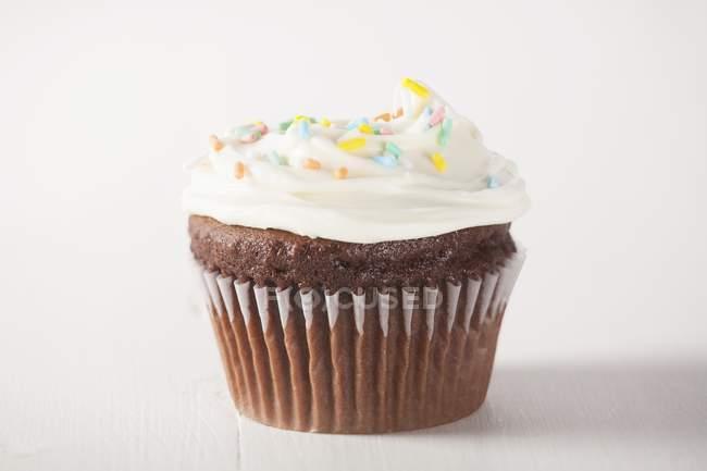 Кекс с белой глазурью и сахар брызгает — стоковое фото