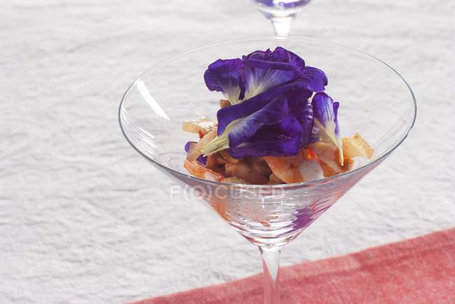 Closeup view of shrimp cocktail with butterfly pea flowers — Stock Photo