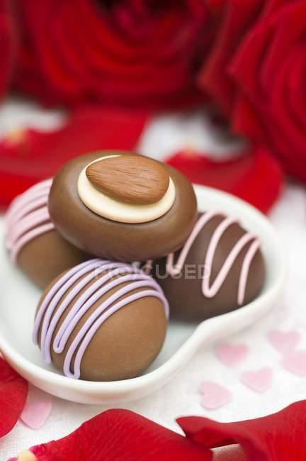 Chocolats dans un plat en forme de cœur — Photo de stock
