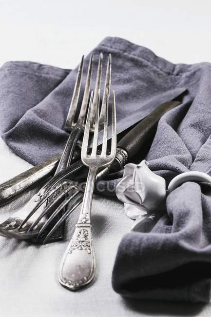Closeup view of old silver cutlery with a grey napkin on a white tablecloth — Stock Photo