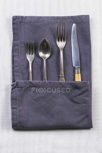 Closeup top view of old silver cutlery in a grey napkin on a white table cloth — Stock Photo