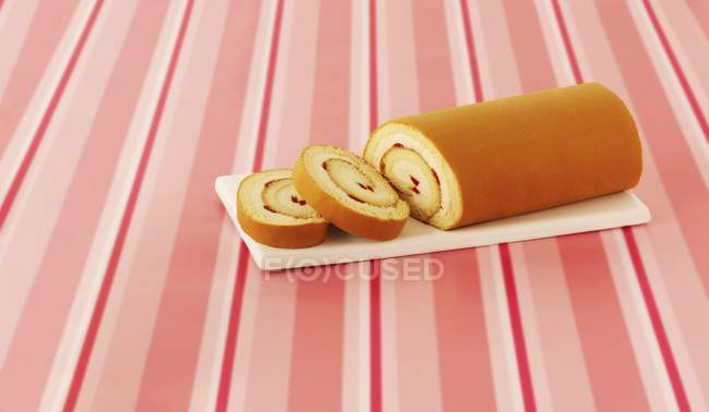 Closeup view of sliced Swiss roll with strawberry cream — Stock Photo