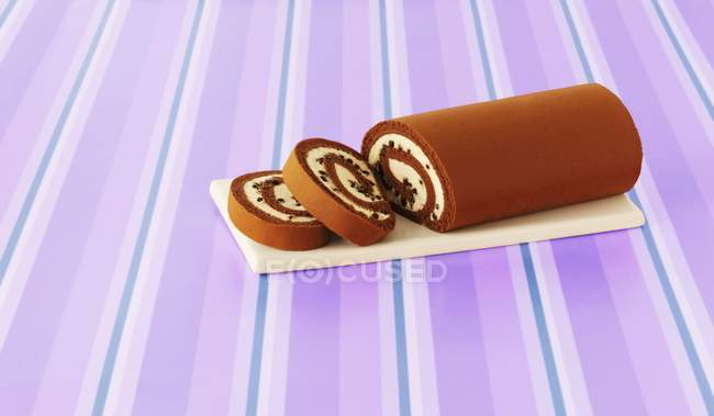 Elevated view of sliced chocolate roll on striped lilac surface — Stock Photo