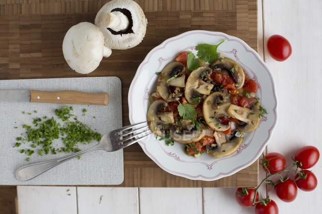 Fried mushrooms with tomatoes and parsley  on white plate over wooden desk with fork and knife — Stock Photo