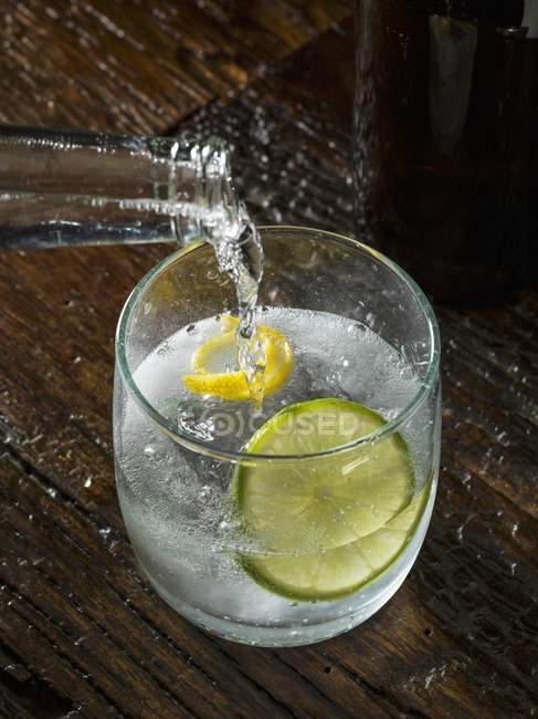 Closeup view of pouring Tonic water to a glass of Gin — Stock Photo