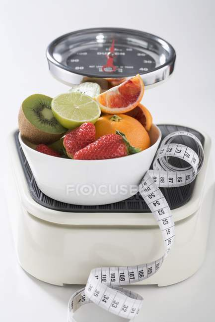 Closeup view of fresh fruit and tape measure on scales — Stock Photo