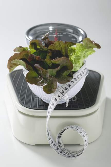 Bowl of lettuce with tape measure — Stock Photo