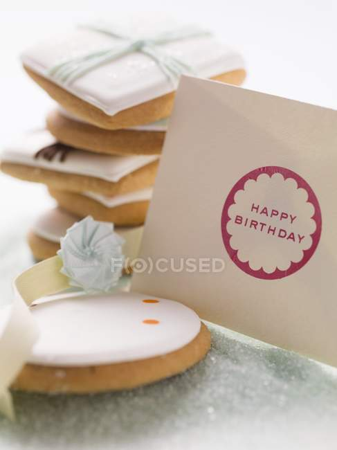 Closeup view of iced biscuits and paper envelope with happy birthday words — Stock Photo