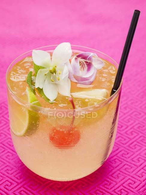 Bebida con lima y flores exóticas - foto de stock