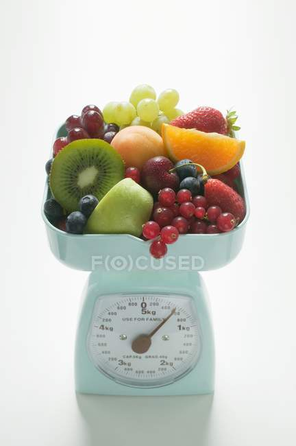 Fruits and berries on kitchen scales — Stock Photo