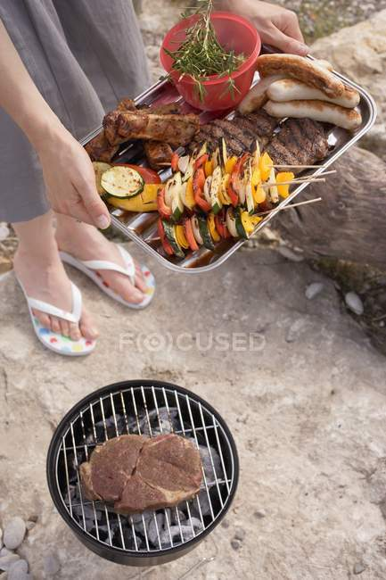Cropped view of woman serving grilled food in aluminium dish at barbecue — Stock Photo