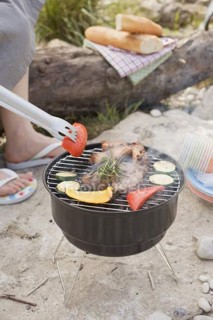 Cropped daytime view of person barbecuing vegetables and meat — Stock Photo
