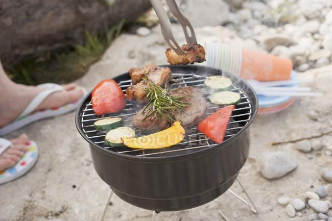 Woman barbecuing food — Stock Photo