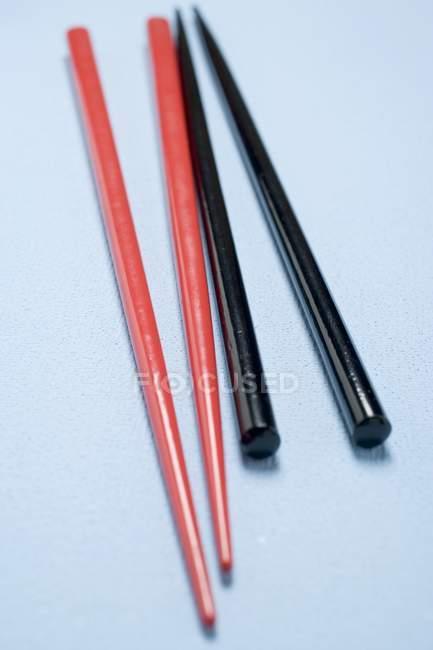 Vue rapprochée des baguettes rouges et noires sur la surface bleu clair — Photo de stock