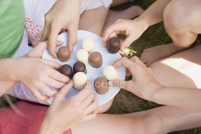 Mãos que procuram marshmallows — Fotografia de Stock