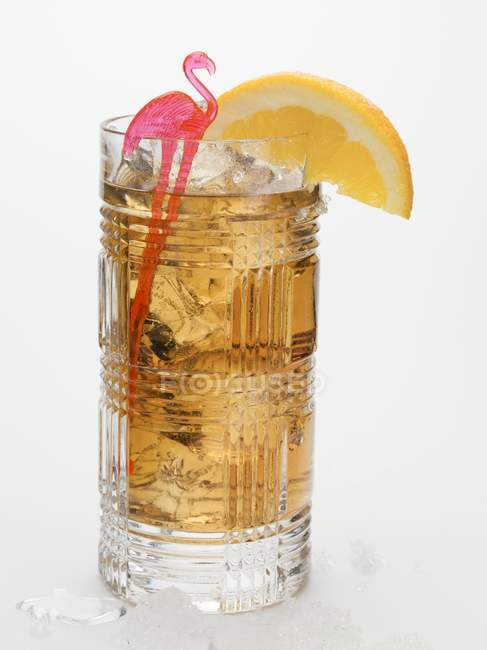 Rum drink with ice cubes and orange wedge — Stock Photo