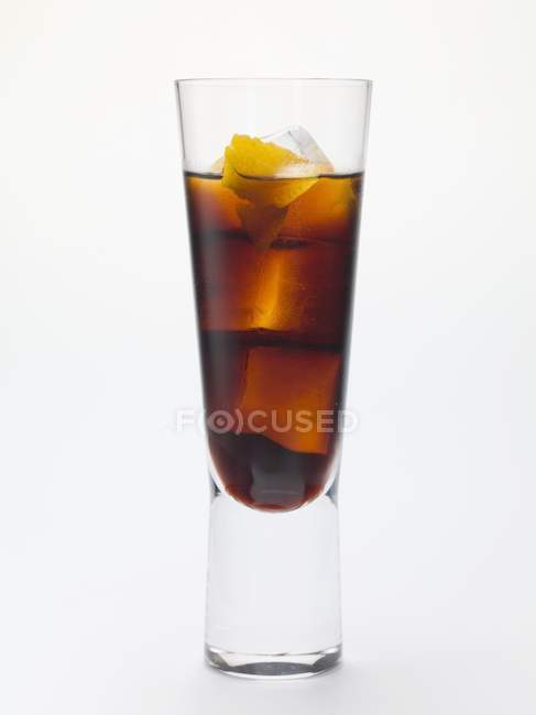 Bitter Schnapps with ice cubes in glass on white surface — Stock Photo