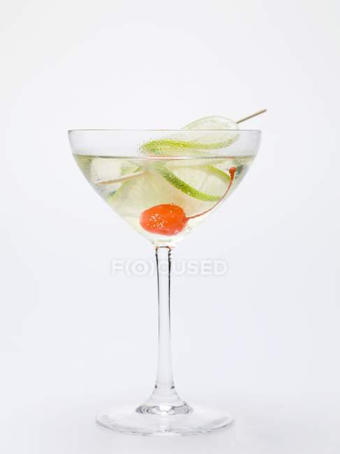 Drink with cocktail cherry and lime — Stock Photo