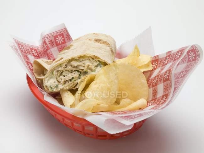 Vista de primer plano de la envoltura con patatas fritas en una cesta de plástico - foto de stock
