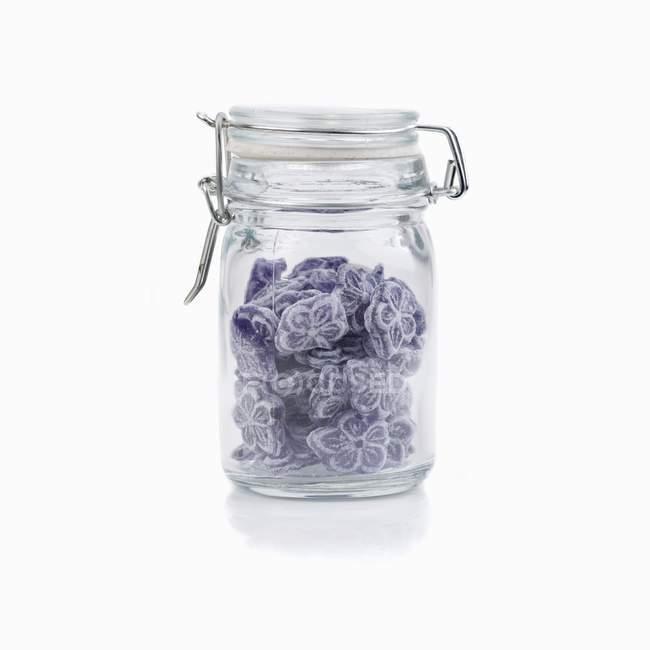 Vue rapprochée des bonbons dans un bocal de conservation en verre sur fond blanc — Photo de stock