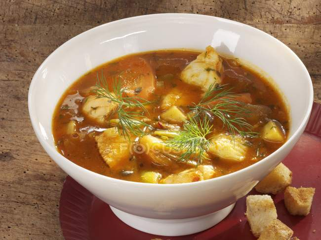 Fish soup in bowl with croutons — Stock Photo