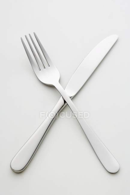 Closeup view of crossed knife and fork on white surface — Stock Photo