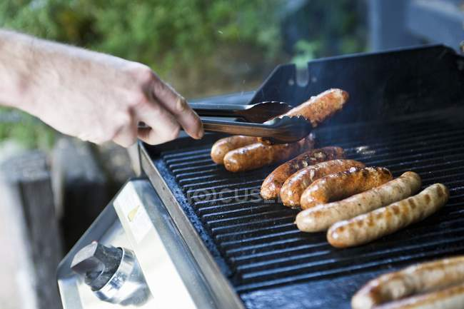 Man cooking Sausages on barbecue — Stock Photo