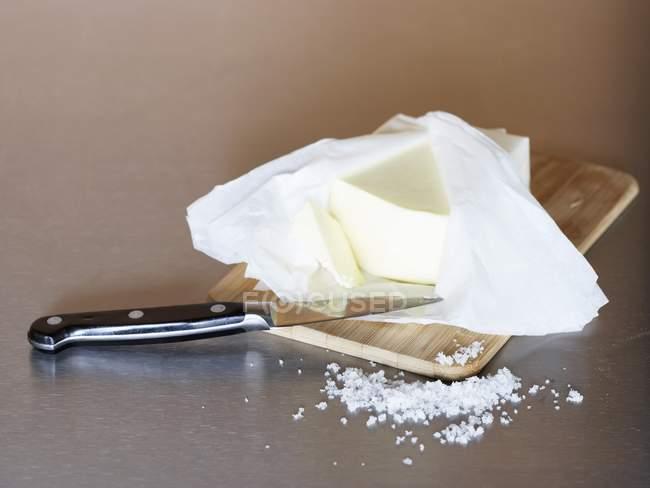 Крупним планом подання вершкового масла у відкритих упаковки на дерев'яну шахівницю з сіллю — стокове фото