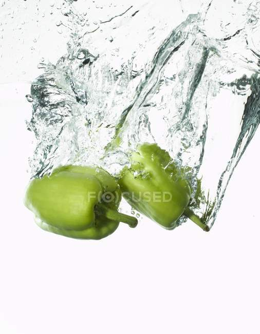 Peppers falling into water — Stock Photo