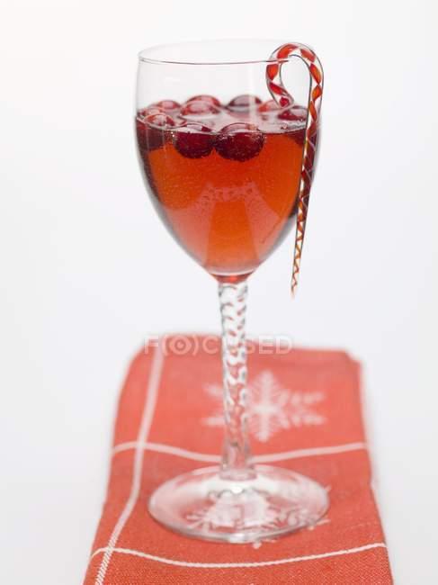 Vista close-up de bebida de cranberry com cana-de-açúcar em vidro — Fotografia de Stock