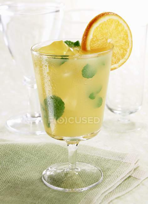 Closeup view of iced drink with mint and orange in glass — Stock Photo