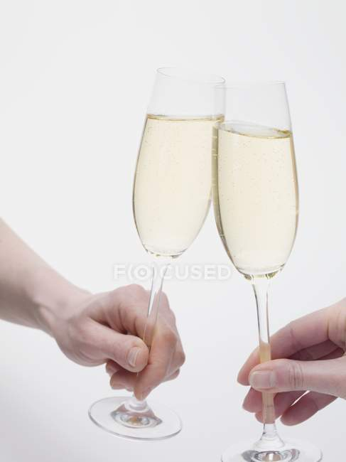 Hands clinking glasses of sparkling wine — Stock Photo
