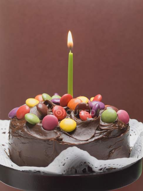 Cake with chocolate and candle — Stock Photo