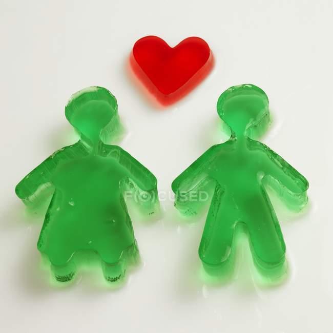 Coração de geleia vermelha e figuras verdes — Fotografia de Stock