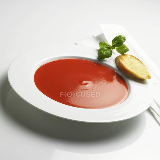 Tomato soup with toast and basil — Stock Photo