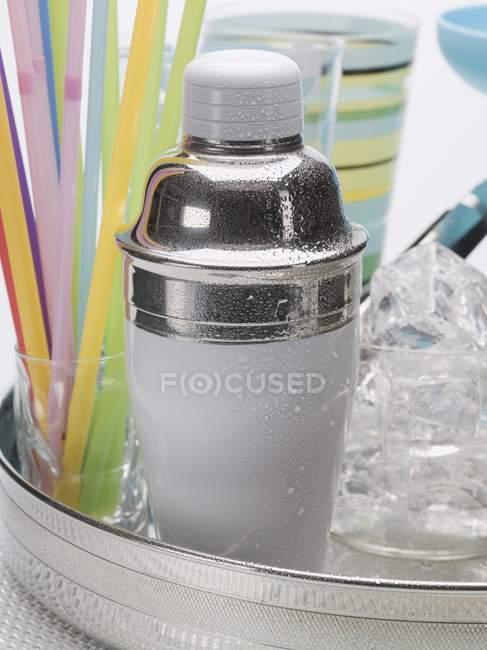 Vue rapprochée du shaker à cocktail avec glaçons, verres et pailles — Photo de stock