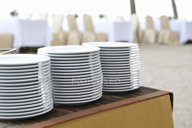 Closeup view of piled plates on a buffet table — Stock Photo