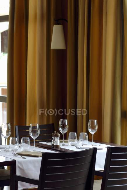 Laid table in a restaurant with curtains on a background — Stock Photo