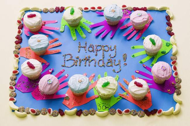 Birthday cake topped with cupcakes — Stock Photo