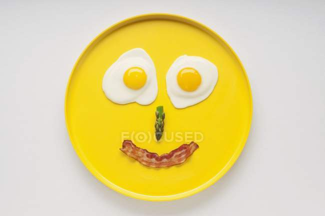 Smiley Face on a Yellow Plate Made from Two Fried Eggs, Asparagus and a Strip of Bacon — Stock Photo