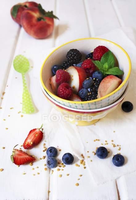 Detailansicht der bunten Obstsalat mit frischer Minze und gehackten Nüssen — Stockfoto