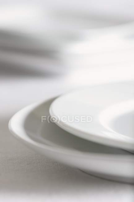 Closeup view of stacked white plates — Stock Photo