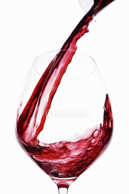 Червоне вино будучи наливало в скло — стокове фото
