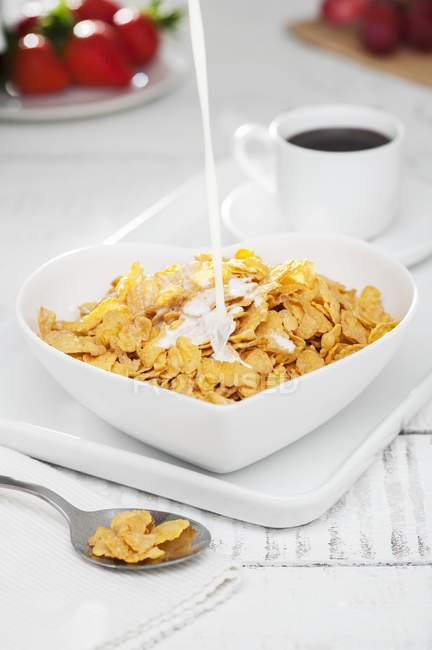 Milk being poured into cornflakes — Stock Photo