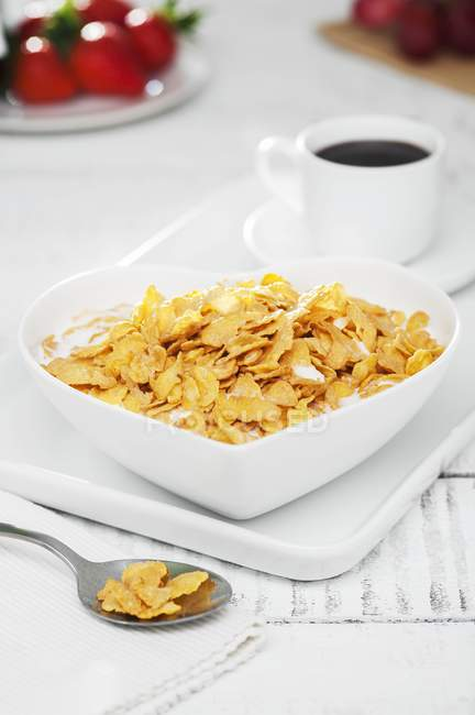 Cornflakes with milk in bowl — Stock Photo