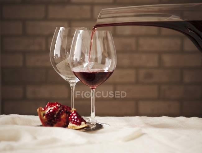 Красное вино, вливаются в стакан — стоковое фото