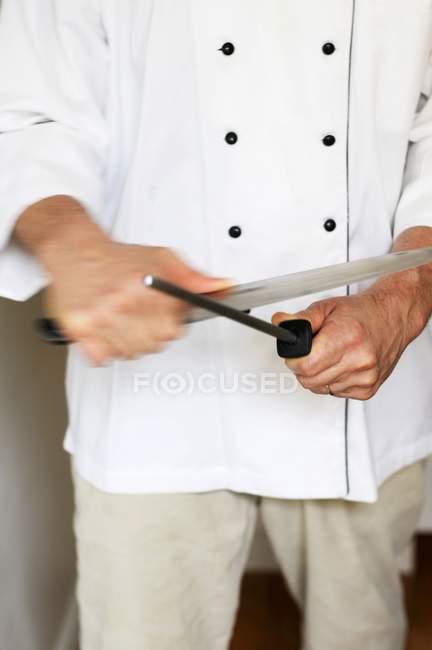 Primo piano vista di uno chef che affila un coltello — Foto stock