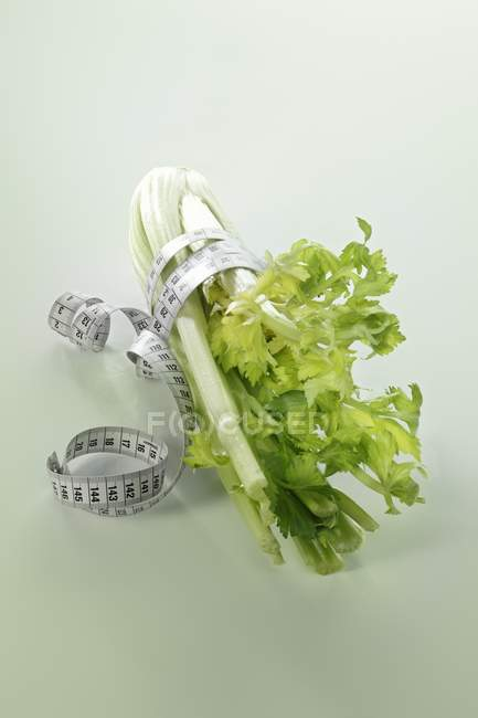Fresh celery and measuring tape — Stock Photo